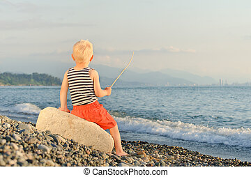 Boy in striped t-shirt sitting on the beach with a stick. Back view