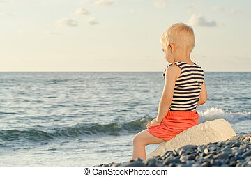 Boy in striped vest sits on a rock by the sea. Back view