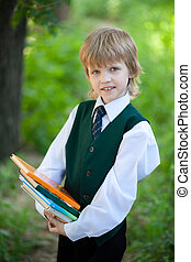 boy in suit holding books in the park