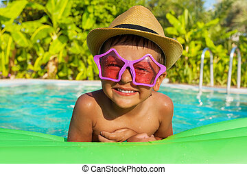 Boy in sunglasses on green airbed, swimming  pool
