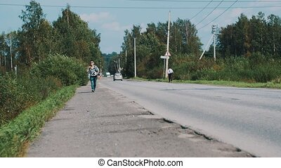 Boy in sunglasses walking along road with map. Travel. Hitchhiking. Thumb up