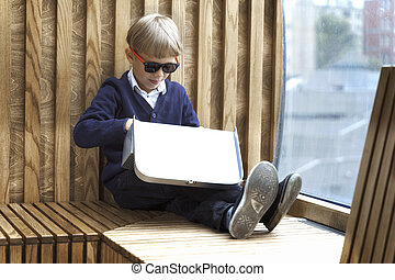 boy in sunglasses with a suitcase sits by the window