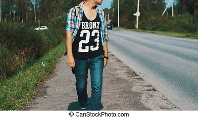 Boy in sunglasses with backpack walking along roadside. Hitchhiking. Thumb up