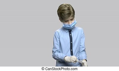 Boy in surgical mask puts on rubber gloves. Little boy...