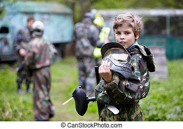 Boy in the camouflage holds a paintball gun barrel up in one...