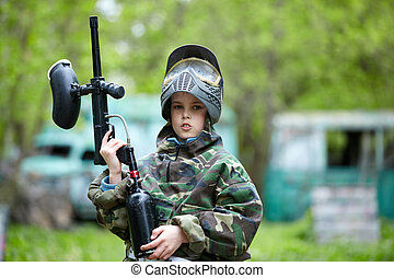 Boy in the camouflage holds a paintball gun barrel up and says something, standing on the paintball ground with old lorry and bus on the background.