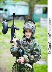 Boy in the camouflage suit holds a paintball gun barrel up and says something, standing on the paintball ground with old lorry and bus on the background.