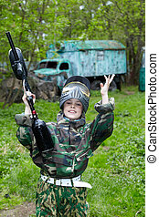 Boy in the camouflage suit, with a smile on his face triumphantly raised his hands and paintball gun up