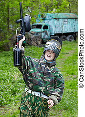 Boy in the camouflage with a smile on his face joyfully cries  and triumphantly raises his hand with a paintball gun up