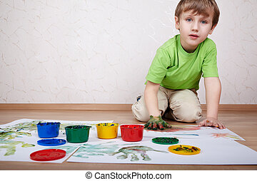 Boy in the green t-shirt draws color paints and makes handprints on the sheet of white paper