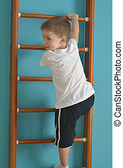 boy in the gym climbing the ladder
