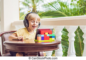 boy in tropics talking with friends and family on video call using a tablet and wireless headphones