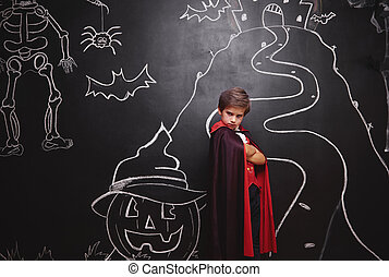 Boy in vampire costume posing