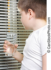 Boy in white looking to window