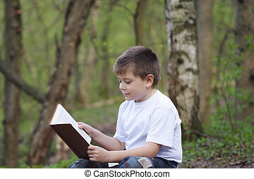 Boy in white reading book in forest