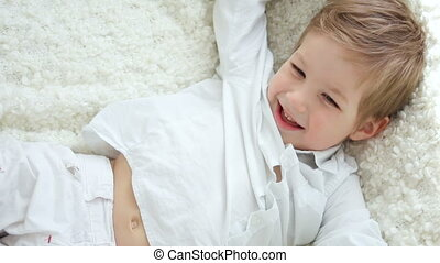 boy in white shirt is lying on the couch bright