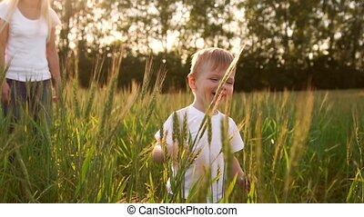 Boy in white shirt walking in a field directly into the...