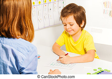 Smiling small boy in yellow T-shirt coloring the paper with pencil at the table indoors