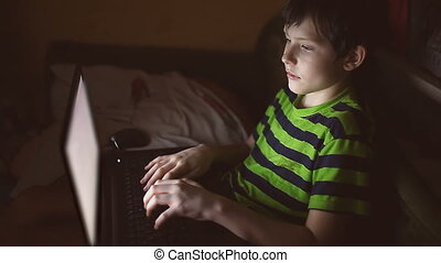boy indoor teen with laptop plays computer game on Internet...
