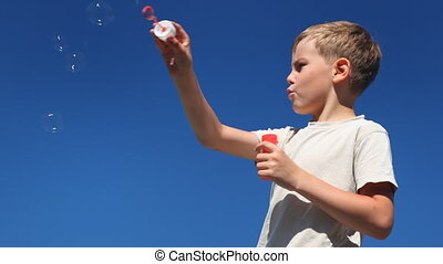 boy inflates bubbles first wave of hand, and then just blowing by mouth