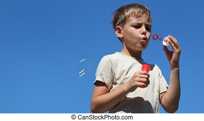 boy inflates different bubbles against blue sky in clear...