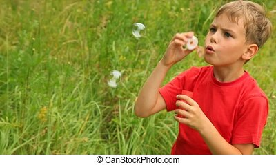 boy is enthusiastically blowing bubbles in park