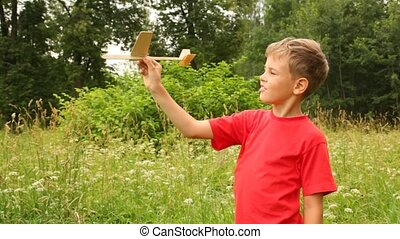 boy is flying out the model of plane in park