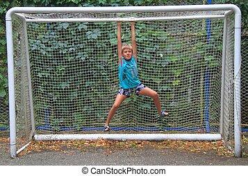 boy is hanging on framework of goal
