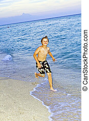 boy is jogging at the beautiful beach