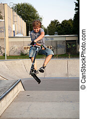 boy is jumping with a scooter over a spine in the skate parc...