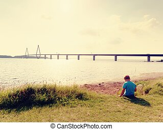 Boy is playing game on offshore, view to the big traffic bridge over bay . The two road bridge with high towers