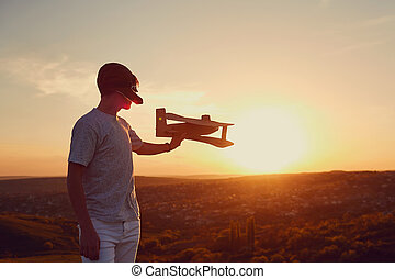 Boy is playing with an airplane on the nature at sunset.