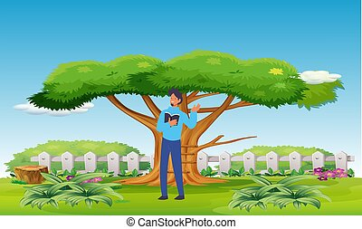 boy is reading a book standing in a park near the tree