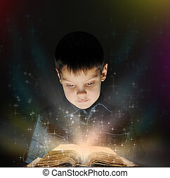 Boy is reading a magic book in the dark on a black...