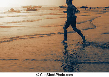 Boy is running into the sea.