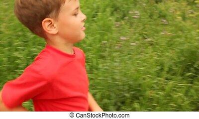 boy is running merrily across a field