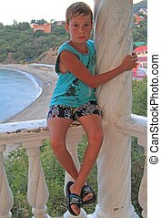 boy is sitting on banister against the background of beach