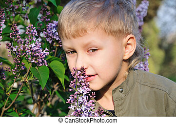 boy is smelling a lilac