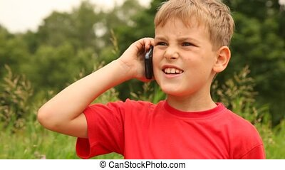 boy is speaking on his mobile phone in the park