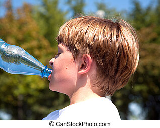 boy is sweating and thursty and drinks mineral water - young...