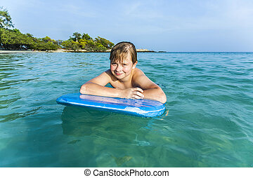 boy is swimming on his surfboard