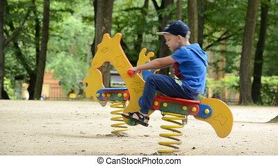 Boy is swinging on playground