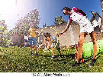 Boy jump through hula hoop ring on playground