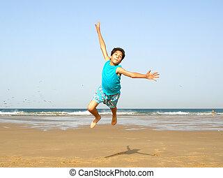 boy flying on the beach