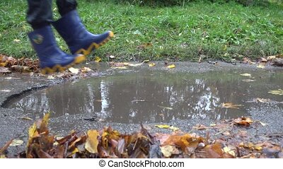 Boy jumping in muddy puddle, slow motion 250 fps