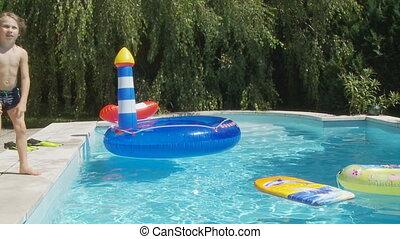 boy jumping in pool slo mo - boy jumping in swimmingpool in...