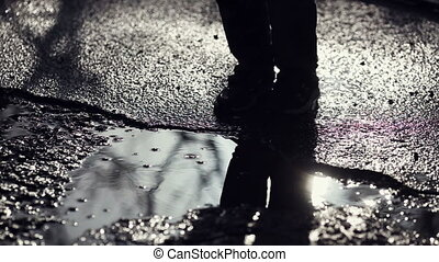 A boy jumping into a puddle. Slow motion.