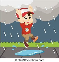 boy jumping in rain on a puddle