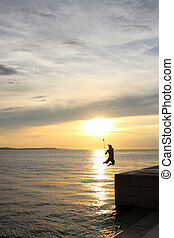 boy jumping in the sea of Croatia