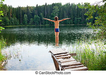 Boy jumping into forest lake - Kid jumps off a wooden dock...